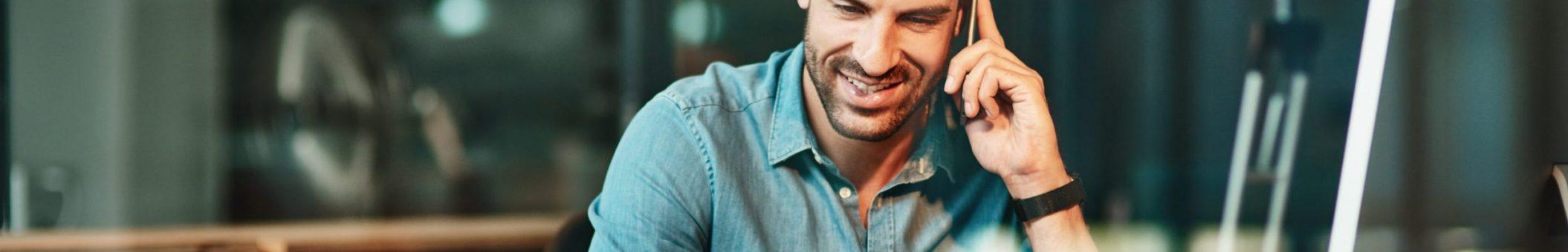 Mann mit Smartphone und Laptop im Büro während Abo-Optimierung bei Alptel