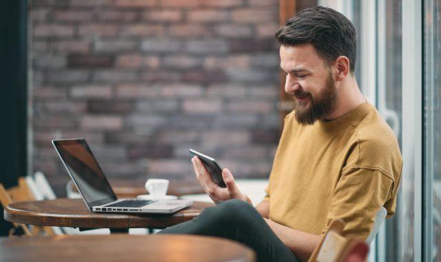 Mann mit Smartphone & Laptop während Telefon-Beratung Mobile von Alptel