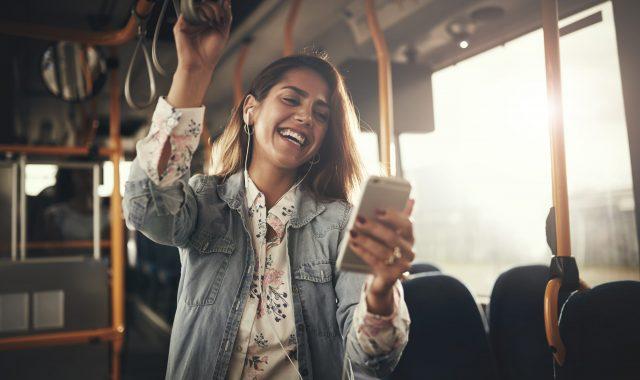 Lachende Frau in Bus mit optimalem Mobile-Abo von Alptel
