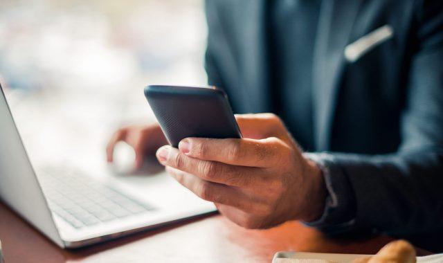 Mann mit Smartphone & Laptop mit optimalem Mobile Abo für Start-up